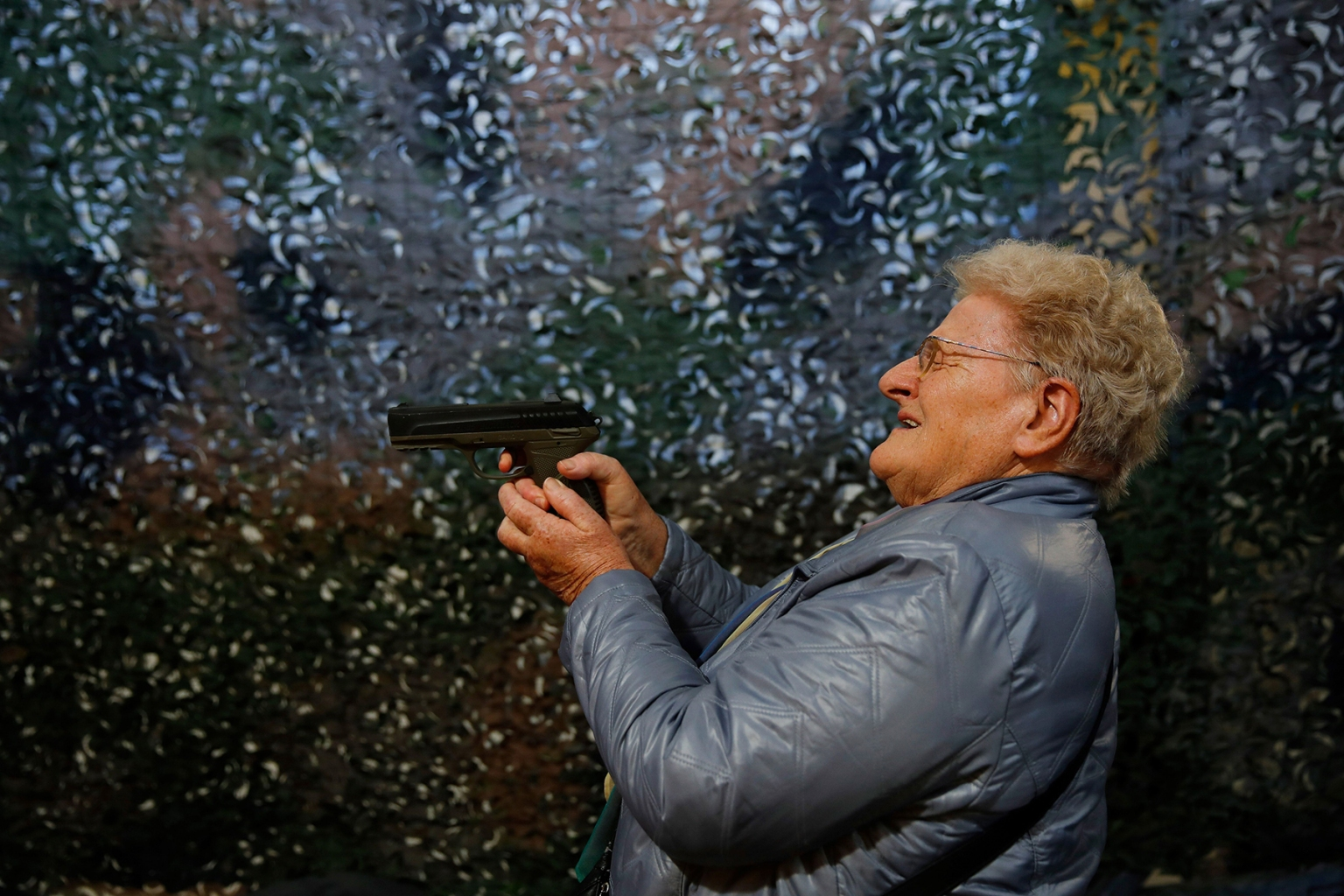 A visitor tries a handgun during the annual Arms Trade Fair in Lucerne, Switzerland, on March 29.  In a country where compulsory military service means many are comfortable with weapons, voters might, in a May 2019 referendum, push back against gun reforms demanded by the European Union. STEFAN WERMUTH/AFP/Getty Images