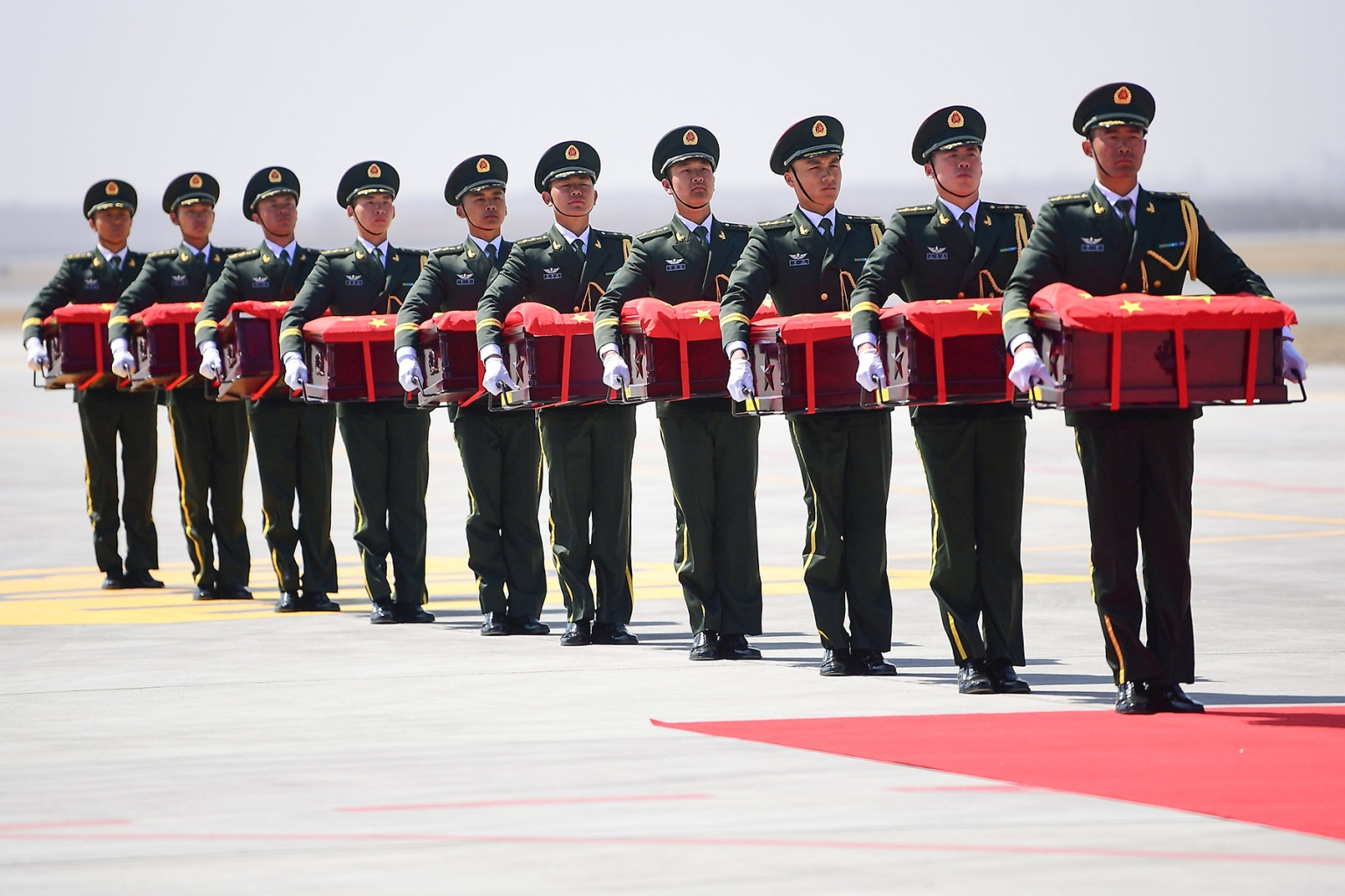 Chinese honor guards carry caskets containing the remains of Chinese soldiers at the Shenyang Taoxian International Airport in Shenyang on April 3. The remains of 10 Chinese soldiers killed during the 1950-53 Korean War were returned from South Korea for permanent burial. STR/AFP/Getty Images