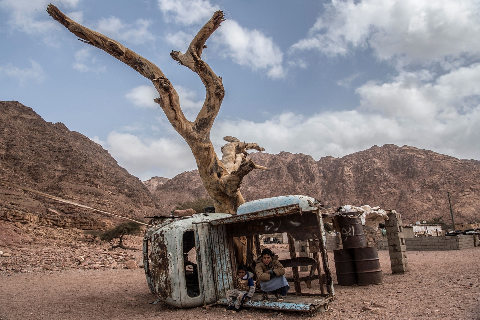 Egyptian Bedouin children sit in a rusted shell of a truck in the village of al-Hamada in Wadi el-Sahu, a village in the southern part of Egypt's eastern Sinai peninsula, on March 30. KHALED DESOUKI/AFP/Getty Images