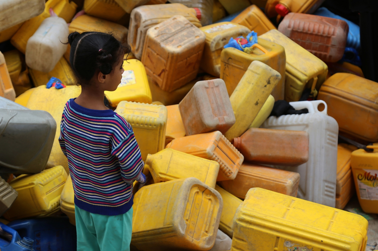 A Yemeni girl looks at plastic containers as people wait to collect water from a tank in the southwestern Yemeni city of Taez on April 3. AHMAD AL-BASHA/AFP/Getty Images