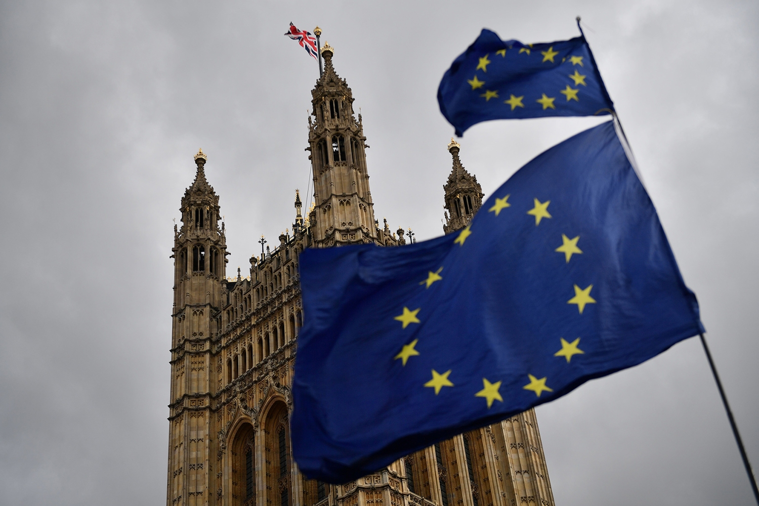 The Union flag flies atop the Houses of Parliament as Brexit demonstrators wave European Union flags in central London on April 4. DANIEL LEAL-OLIVAS/AFP/Getty Images)