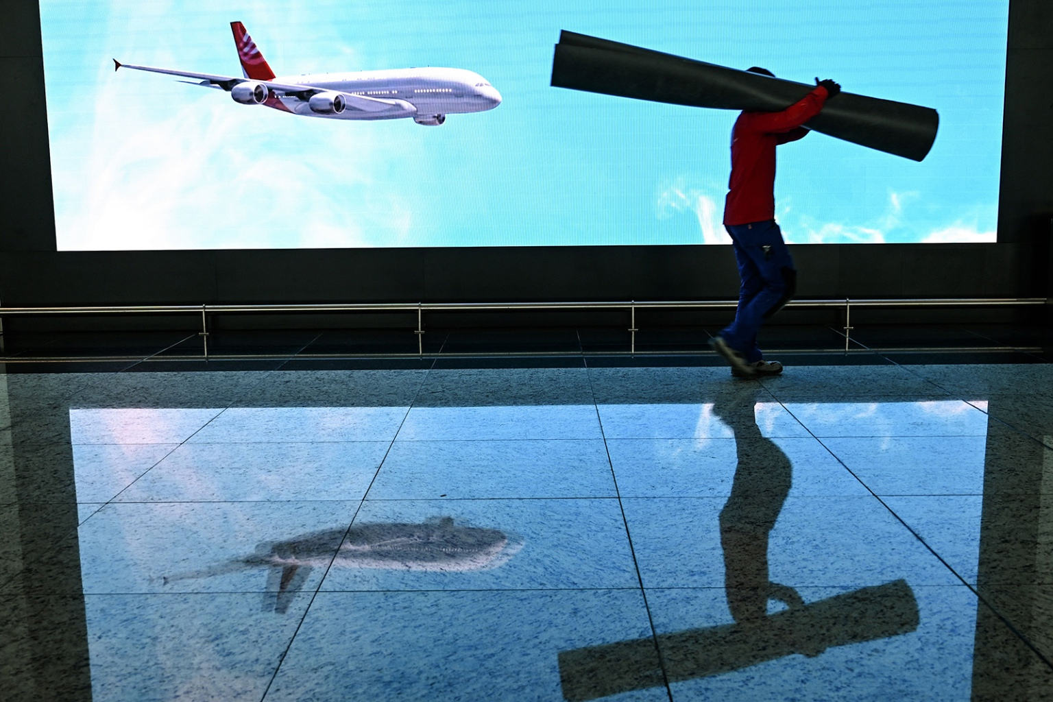A worker carries a carpet in front of a screen in a hall of the new Istanbul Airport on the first day after it moved from Ataturk International airport on April 6. The move took 45 hours and involved 707 trucks and 800 staff members to move 10,000 pieces of equipment piece by piece. OZAN KOSE/AFP/Getty Images