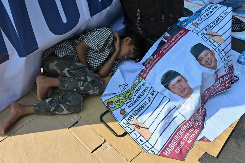 A youth sleeps beside a campaign banner as people gather for an election campaign rally for Indonesian presidential candidate Prabowo Subianto and his running mate Sandiaga Uno outside the Gelora Bung Karno stadium in Jakarta on April 7, 2019. (Adek Berry/AFP/Getty Images)