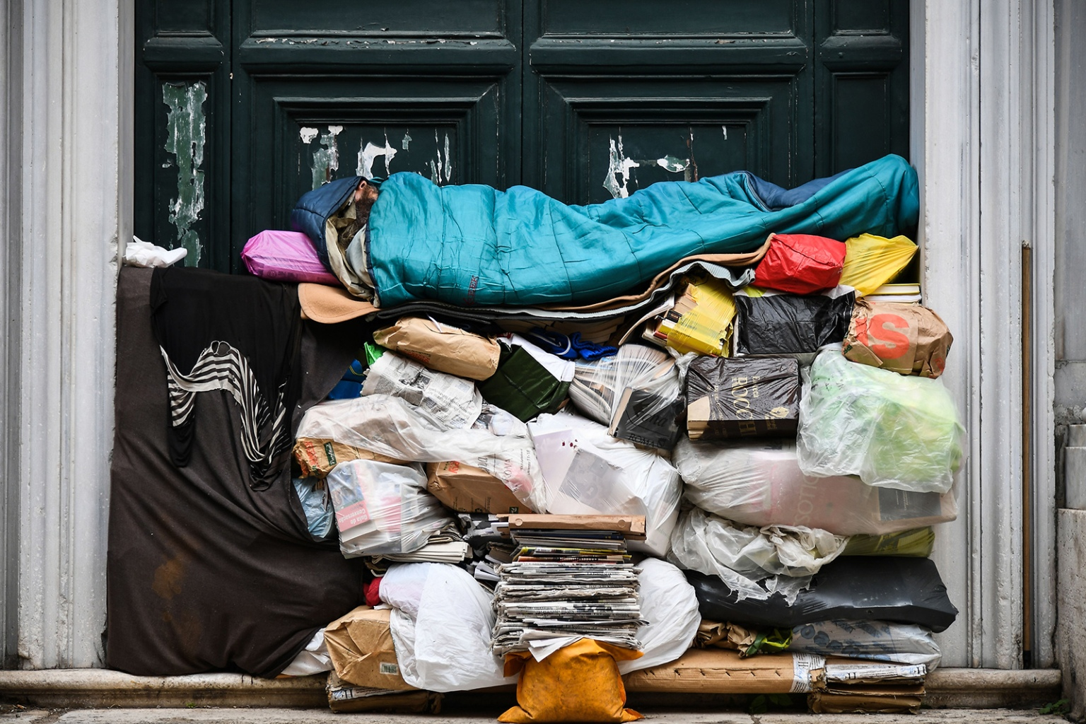 A homeless man sleeps on a pile of plastic bags and newspapers under a porch in Rome on April 7. VINCENZO PINTO/AFP/Getty Images