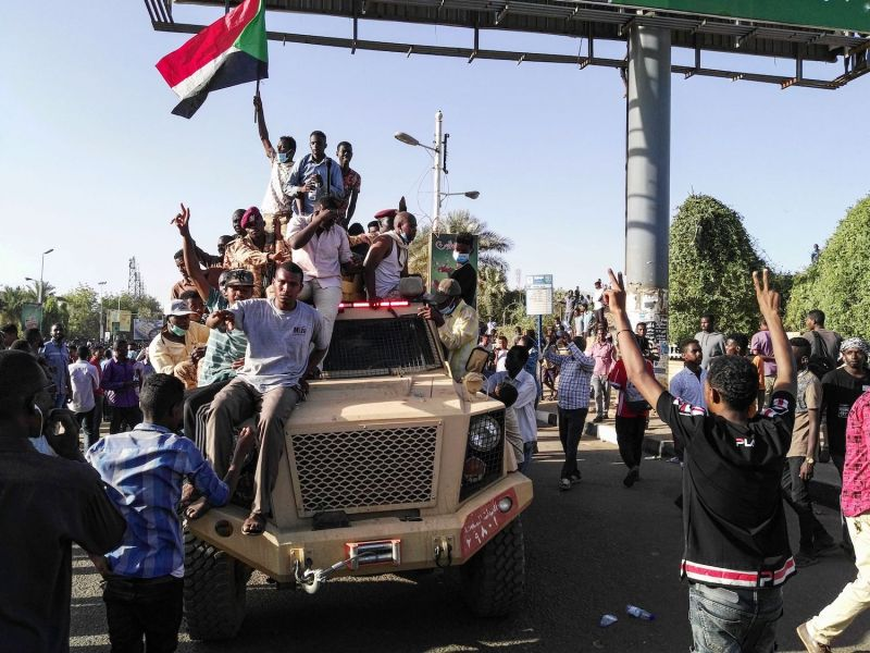 Sudanese protesters wave a national flag atop a military vehicle next to soldiers near military headquarters in Khartoum, Sudan, on April 7. (AFP/Getty Images)