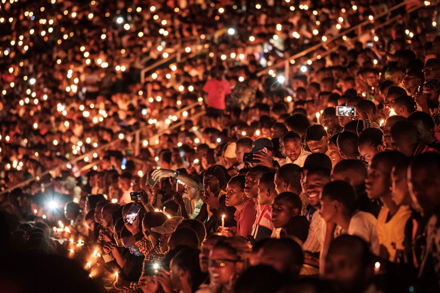 People hold candles as they attend a night vigil and prayer at the Amahoro Stadium as part of the 25th commemmoration of the 1994 genocide in Kigali, Rwanda, on April 7. The country began 100 days of mourning for more than 800,000 people killed in the genocide. YASUYOSHI CHIBA/AFP/Getty Images