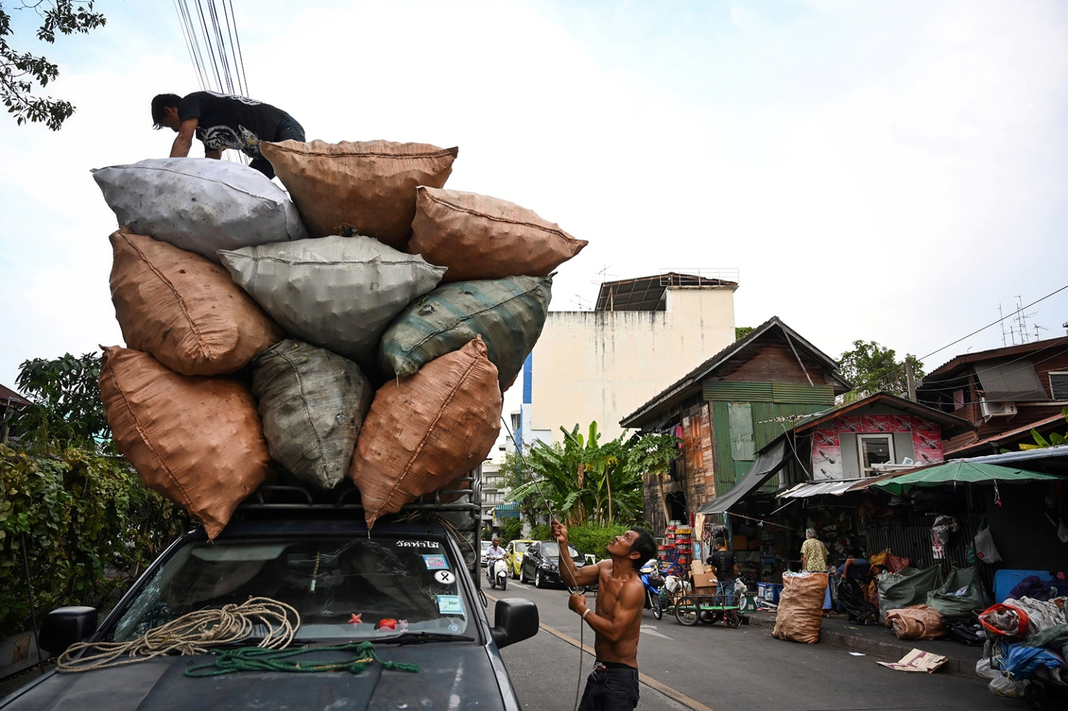 Two men prepare to transport sacks of scrap plastic bottles for recycling in Bangkok on April 9. LILLIAN SUWANRUMPHA/AFP/Getty Images