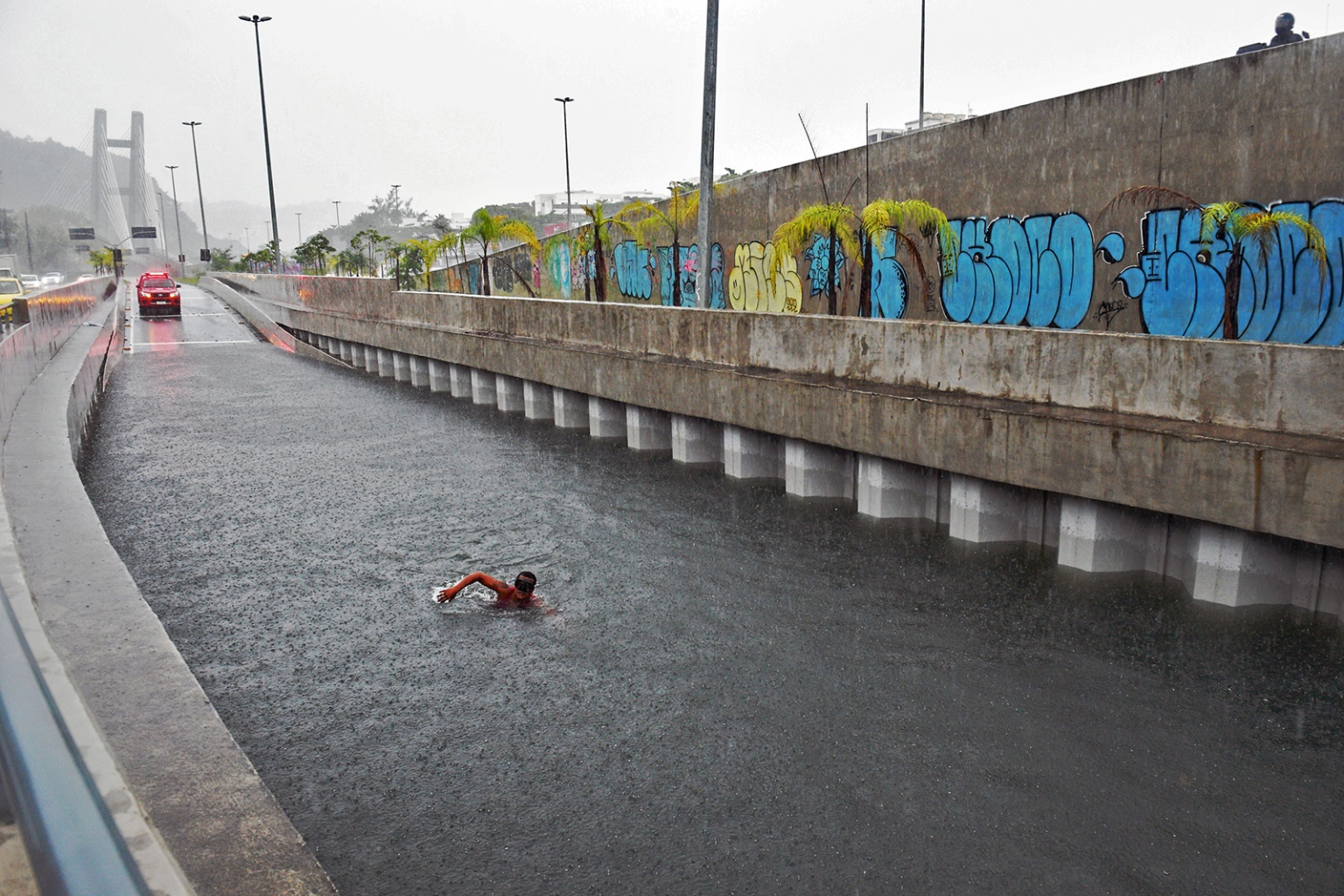 A firefighter of the underwater unit dives to inspect a submerged car at a flooded road tunnel after heavy rains in Rio de Janeiro on April 9. CARL DE SOUZA/AFP/Getty Images