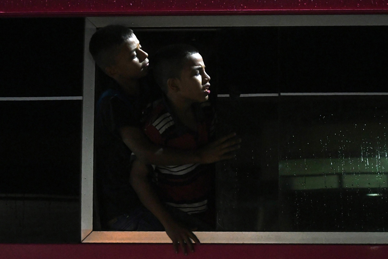 Two Honduran boys look out the window of a bus leaving the Metropolitan Center of San Pedro Sula, to travel to the Guatemala border en route to the United States on April 9. ORLANDO SIERRA/AFP/Getty Images