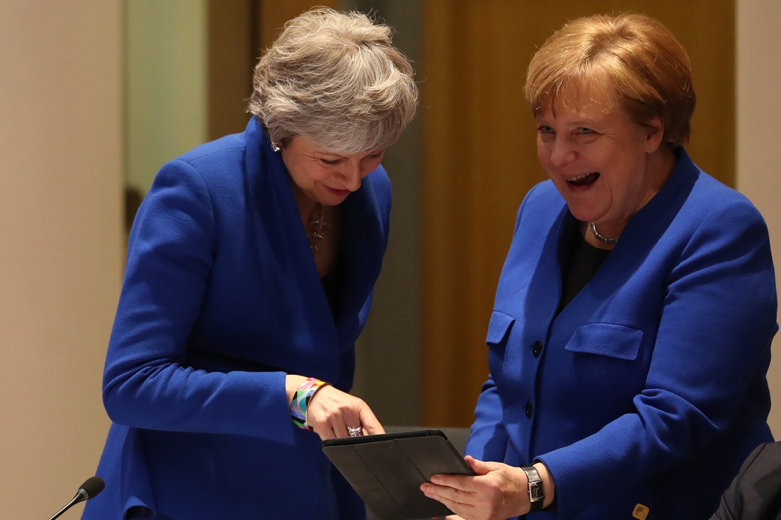 British Prime Minister Theresa May and German Chancellor Angela Merkel look at a tablet ahead of a European Council meeting on Brexit in Brussels on April 10. KENZO TRIBOUILLARD/AFP/Getty Images