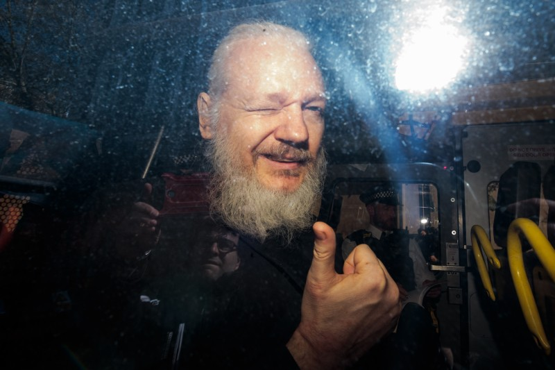 Julian Assange gestures to the media from a police vehicle on his arrival at Westminster Magistrates court in London on April 11. (Jack Taylor/Getty Images)