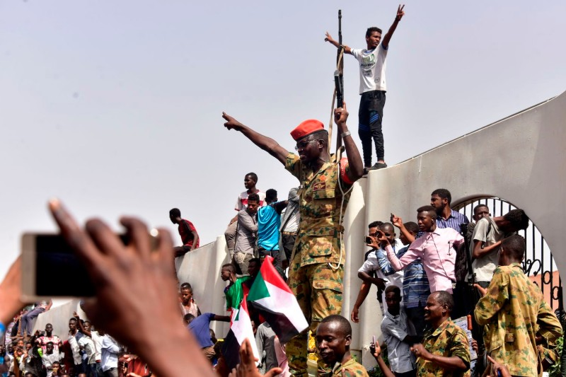 After Sudanese President Omar al-Bashir was ousted, members of the Sudanese military gather in a street with protestors in central Khartoum on April 11. (Ahmed Mustafa/AFP/Getty Images)