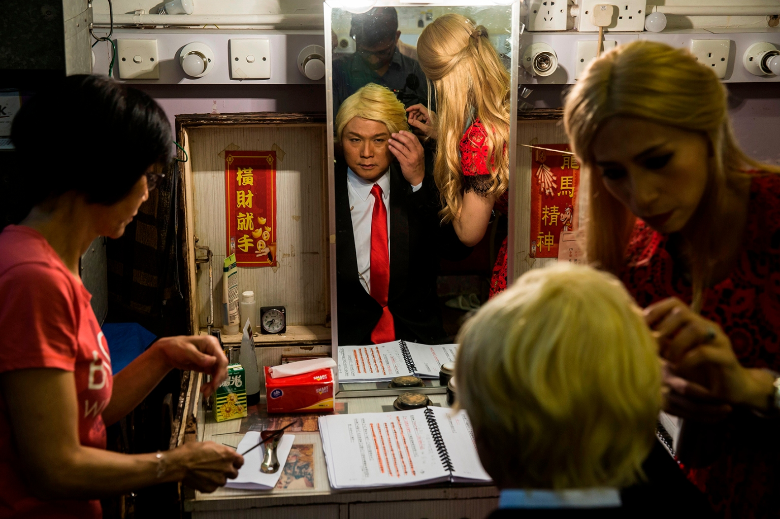 """Actress Man Chan, dressed as Ivanka Trump, helps actor Loong Koon-tin dress as U.S. President Donald Trump backstage during a rehearsal of a Cantonese opera called """"Trump on Show"""" in Hong Kong on April 11. ISAAC LAWRENCE/AFP/Getty Images"""