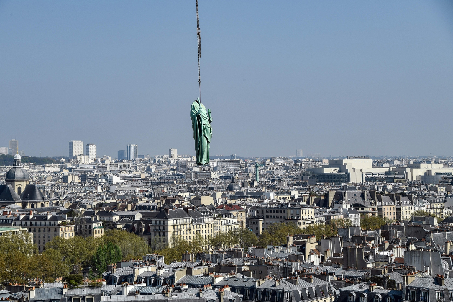 TOPSHOT - A crane lifts one of 16 copper statues, sitting 50 meters above the ground, off the Notre-Dame-de-Paris Cathedral to be taken for restoration on April 11, 2019 in the French capital Paris. - Using a 120 meter crane at the foot of the cathedral, the sixteen statues, the 12 apostles and the 4 evangelists, which sit around the spire of the cathedral are being removed to be sent to Perigueux, in southwest France for restoration. The absence of the statues will also signal the start of the renovation work of the spire that will last until 2022. Only then will the statues,  commisioned in the 1860s during the great restoration of the cathedral by Viollet-le-Duc, return to their original place. (Photo by BERTRAND GUAY / AFP)        (Photo credit should read BERTRAND GUAY/AFP/Getty Images)