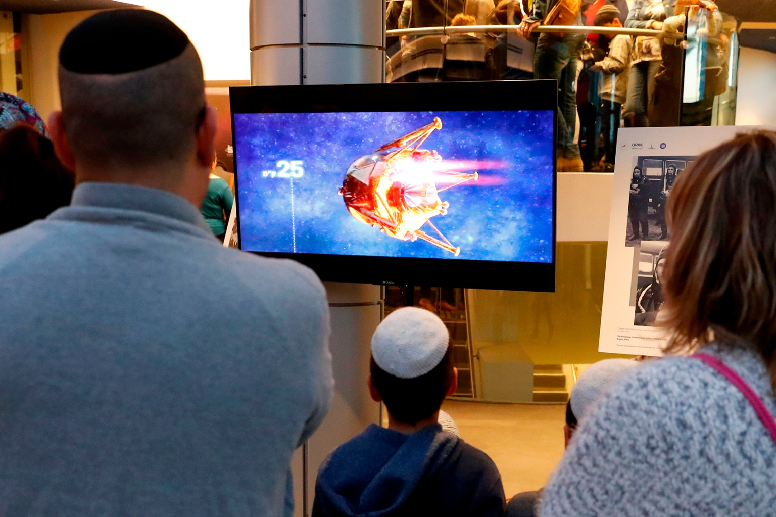 People watch a screen showing explanations of the landing of Israeli spacecraft, Beresheet's, at the Planetaya Planetarium in the Israeli city of Netanya before it crashed during landing on April 11. JACK GUEZ/AFP/Getty Images