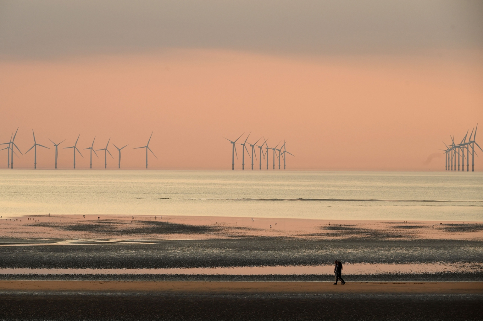 People walk on the beach at sunset with the Burbo Bank wind farm on the Irish Sea in the background at New Brighton, England, on April 11. PAUL ELLIS/AFP/Getty Images