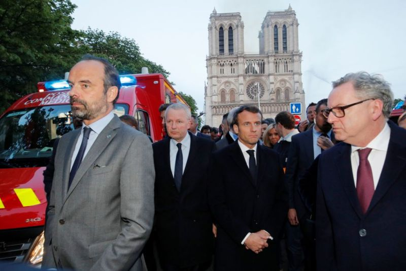 French Prime Minister Edouard Philippe, and French President Emmanuel Macron near the entrance of the Notre-Dame de Paris Cathedral in Paris, as flames engulf its roof on April 15, 2019. (Philippe Wojazer/AFP/Getty Images)