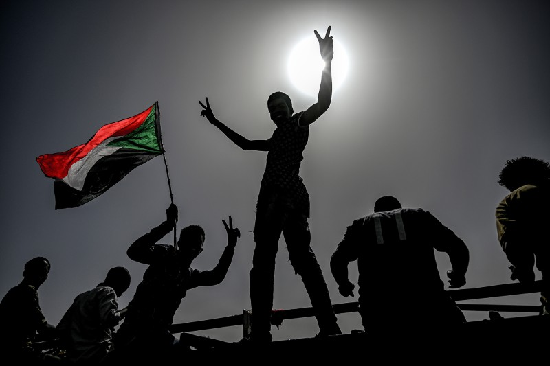 Sudanese protesters wave flags and flash victory signs as they protest outside the army complex in the capital Khartoum on April 17. OZAN KOSE/AFP/Getty Images
