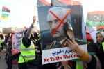 A Libyan woman hits a photo of strongman Khalifa Haftar with her shoe during a demonstration in Tripoli on April 19.