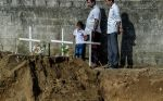 A child looks at a grave after a funeral for victims of the Easter Sunday attacks in Katuwapity village on April 23, 2019 in Negambo, Sri Lanka.