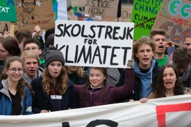 "Swedish teenaged climate activist Greta Thunberg (C) holds up her Swedish ""School Strike for the Climate"" sign as she participates in a Fridays for Future march with German climate activists Luisa Neubauer and Jakob Blasel on March 29, 2019 in Berlin, Germany. (Sean Gallup/Getty Images)"