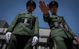 Two paramilitary police officers secure an area along a street during the Belt and Road Forum in Beijing on April 25.