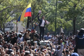 Venezuelan opposition leader Juan Guaidó, recognized by many countries including the United States as the country's rightful interim ruler, stands on top of a car surrounded by soldiers and civilians at Plaza Altamira in Caracas, Venezuela, on April 30.