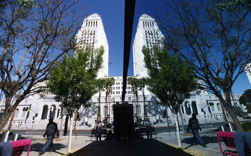 A man is reflected walking outside Los Angeles City Hall on April 25.