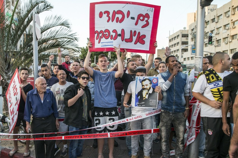 "Israeli far-right demonstrators hold a placard that reads in Hebrew ""The Jewish blood will not be abandoned"" and a poster of the late Meir Kahane, at the scene of an attack in the Israeli city Rishon LeZion on November 2, 2015. (Jack Guez/AFP/Getty Images)"