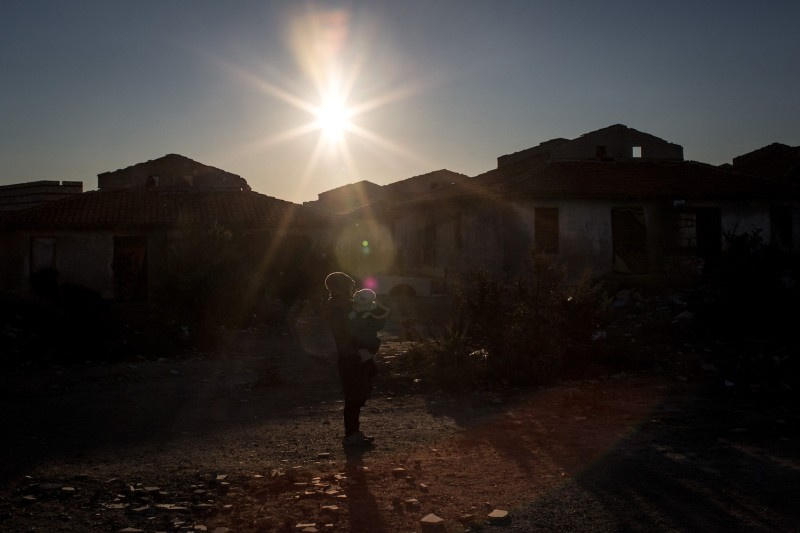 An Afghan refugee stands in the sun with her daughter in the coastal town of Cesme, Turkey, on Dec. 4, 2015. (Chris McGrath/Getty Images)