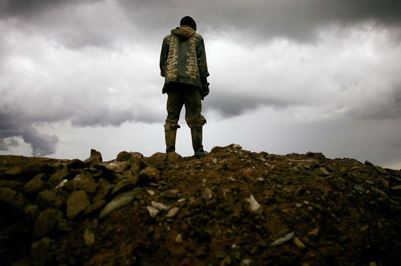 A miner stands on a mound of dirt at an abandoned industrial mine March 28, 2006 in Mongbwalu, Congo. (Spencer Platt/Getty Images)