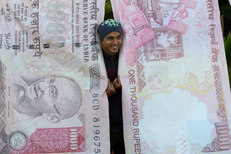 A man poses with replica prints of the demonetized 500- and 1,000-rupee notes in Mumbai on Nov. 20, 2016.