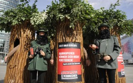 """Performers dressed as trees and hunters stage a demonstration against video piracy in Berlin on Sept. 3, 2008. The placard reads: """"Copyright pirates can't hide, not even on the internet."""""""