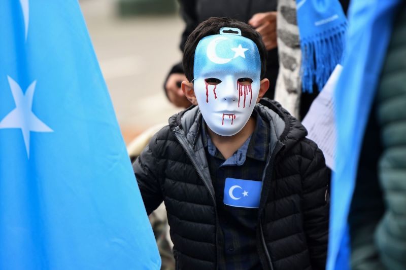A boy wearing a blue mask with tears of blood participates in a protest march demanding the European Union take action against China in support of the Uighurs, in Brussels, on April 27, 2018. (Emmanuel Dunand/AFP/Getty Images)