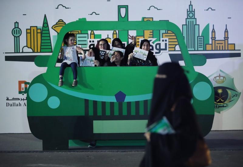Teenage girls pose behind a pretend car in Jeddah, Saudi Arabia, on June 22, 2018.