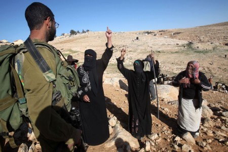Female Palestinian shepherds complain to an Israeli soldier after Israeli settlers harassed them and their sheep near the village of Umm el-Kheir in the southern hills of the West Bank near Hebron on January 25, 2014.