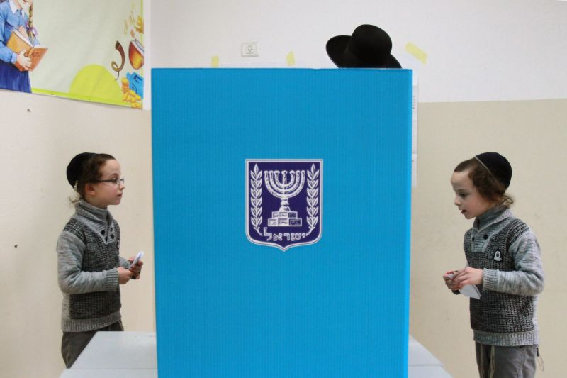 An Ultra-Orthodox Israeli man, accompanied by his children, prepares to cast his ballot at a polling station in Bnei Brak, near the city of Tel Aviv, on March 17, 2015.