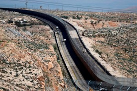 Cars drive on a new Israeli road divided by a wall to separate it for Palestinians (L) and the side to be used exclusively by Israelis and settlers (R) in East Jerusalem, on January 10, 2019. Route 4370 connects the settlement of Geva Binyamin to the Jerusalem-Tel Aviv highway. The road, which has been called the Apartheid Road, is divided in the middle by a 25-foot wall.
