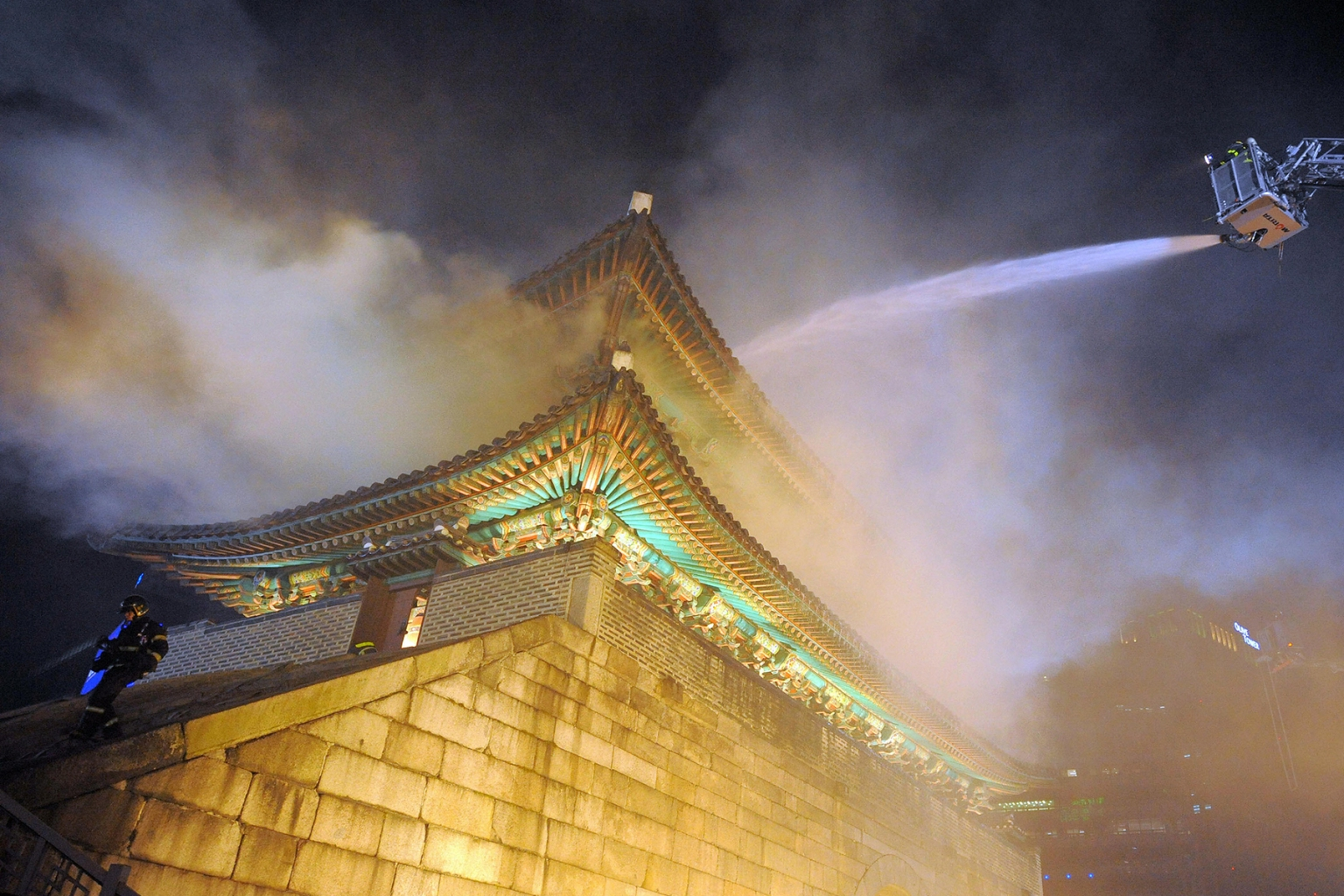 "Firefighters battle a fire at the Namdaemun gate in Seoul on Feb. 10, 2008.  The city's oldest wooden structure, called ""National Treasure No. 1,"" was constructed in 1398, rebuilt in 1447, and had been frequently renovated. Since the fire, set by an arsonist, the gate has been completely rebuilt. (Kim Jae-Hwan/AFP/Getty Images)"