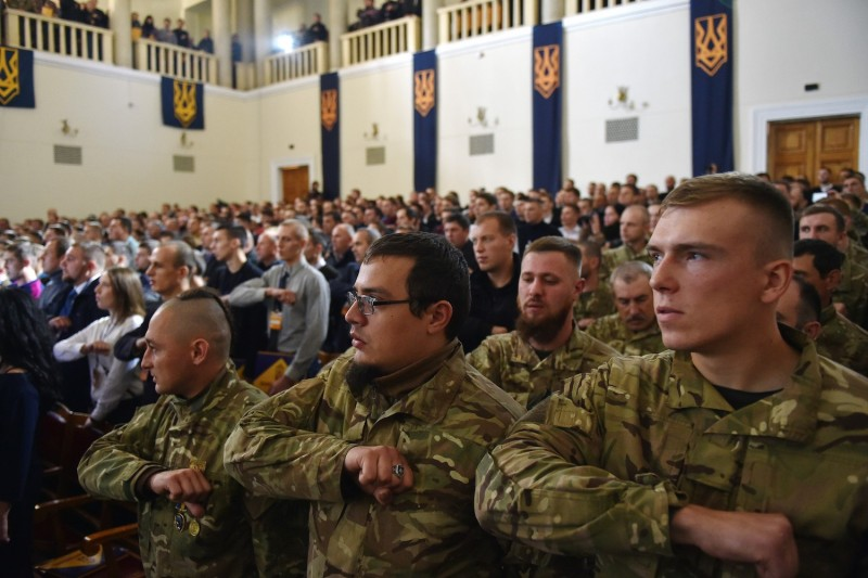 Delegates sing the Ukrainian national anthem during the first congress of the new political party National Corps, created from the members of Azov civil corps and veterans of Azov regiment in Kiev on October 14, 2016.
