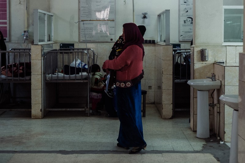 A mother carries her sick child inside the respiratory wing of the Indira Gandhi Children's Hospital in Kabul on Feb. 18.
