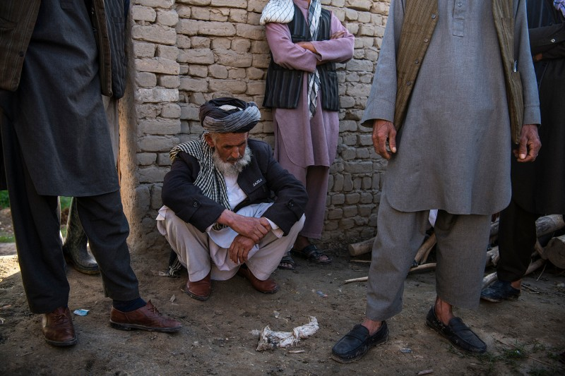Juma Khan gathers with neighbors on March 31 at the site of what appears to be a U.S. airstrike in which 13 members of an extended family, including his daughter, son-in-law, and numerous grandchildren, were killed in the village of Aqulabul, near Telawka, north of Kunduz, Afghanistan, on March 22.