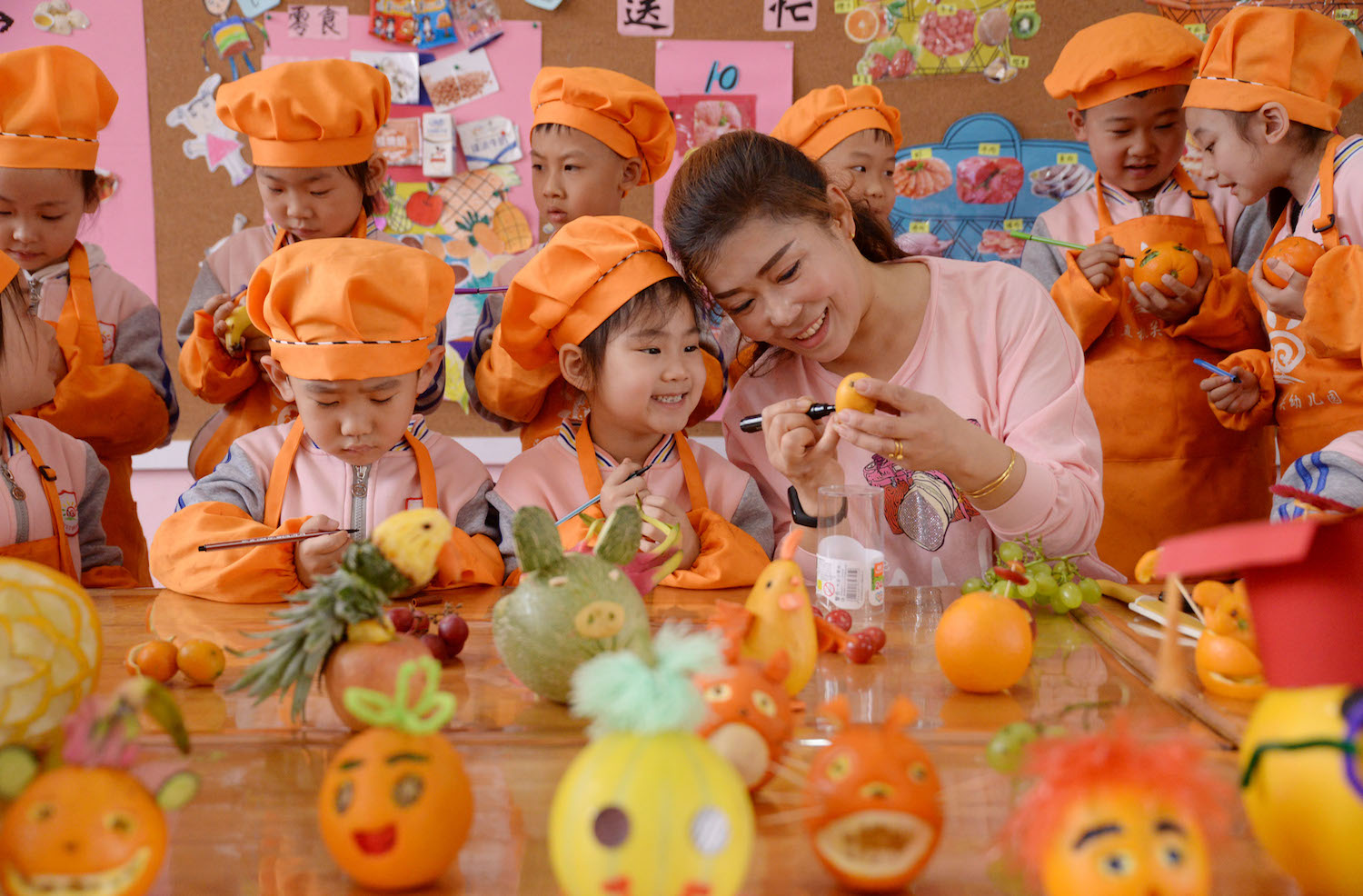 A teacher surrounded by children draws a smiley face on a fruit to welcome World Smile Day at a kindergarten in Handan, China, on May 8.