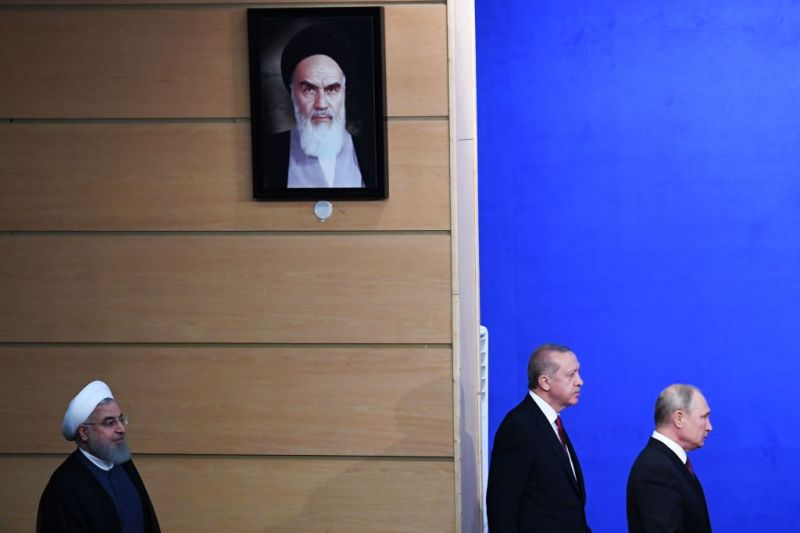 Iranian President Hassan Rouhani, Turkish President Recep Tayyip Erdogan, and Russian President Vladimir Putin walk past a portrait of founder of the Islamic Republic Ayatollah Ruhollah Khomeini as they arrive for a press conference after meeting in Tehran on Sept. 7, 2018.