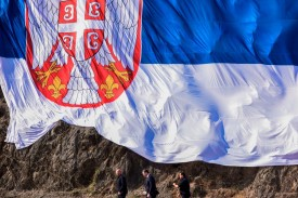 Serbian President Aleksandar Vucic walks under a giant Serbian national flag during his arrival in the village of Gazivode, Serbia on Sept. 8, 2018.