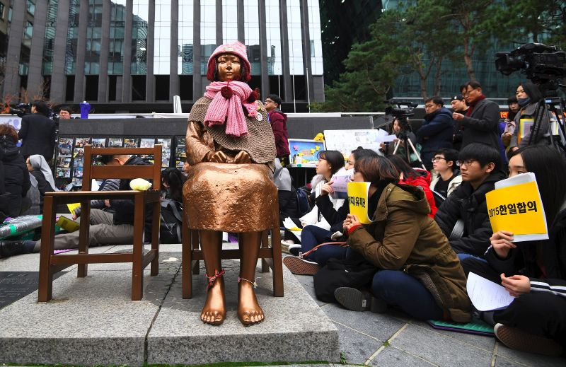 "South Korean protesters sit near a statue of a teenage girl symbolizing former ""comfort women"", who served as sex slaves for Japanese soldiers during World War II, during a weekly anti-Japanese demonstration in front of the Japanese embassy in Seoul on November 21, 2018."