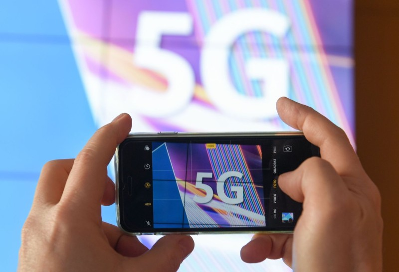 A journalist takes pictures of a projection screen prior to the start of Germany's auction for the construction of an ultra-fast 5G mobile network in Mainz on March 19.