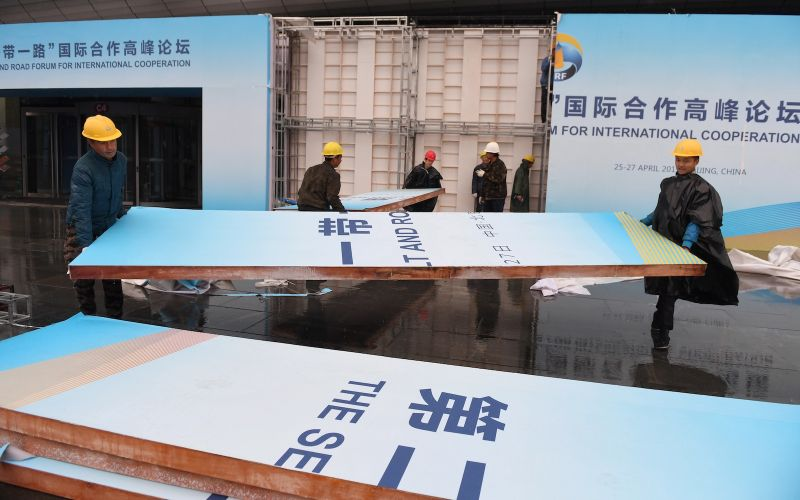 Workers take down a Belt and Road Forum panel outside the venue of the forum in Beijing on April 27, 2019.