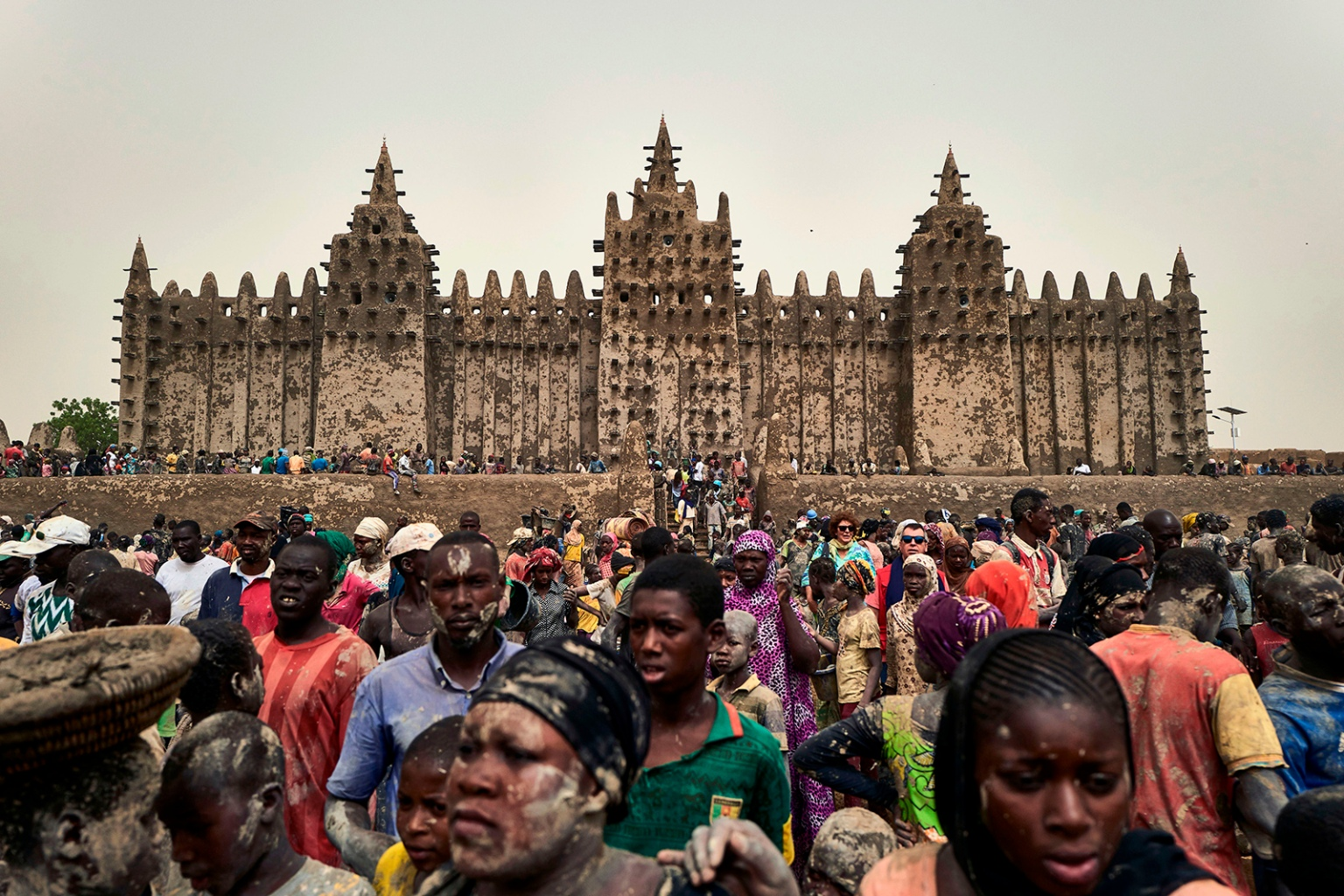 People take part in the annual rendering of the Great Mosque of Djenne in central Mali on April 28. Several thousand residents of the historic city, a UNESCO World Heritage site, render the mosque with banco—a mixture of soil and water, with rice bran, shea butter and baobab powder—to protect it from bad weather ahead of the rainy season. MICHELE CATTANI/AFP/Getty Images