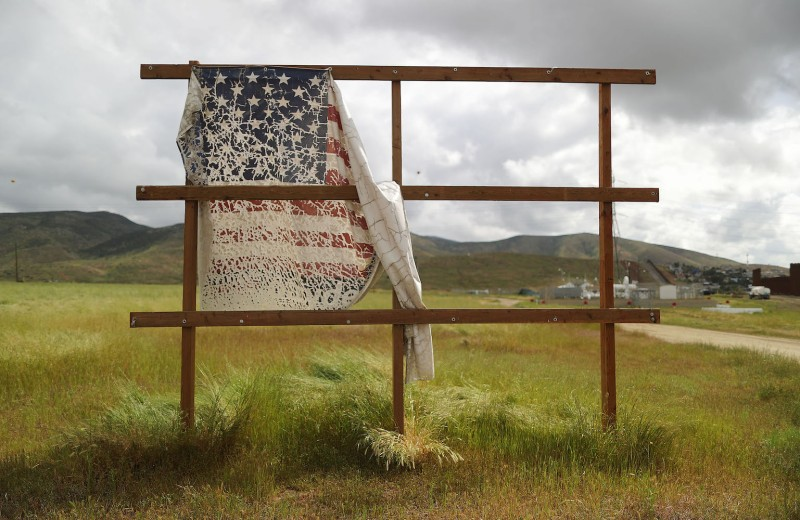 An old billboard displaying a U.S. flag stands on the United States' side of the U.S.-Mexico border in California on April 3.